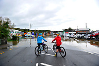 Pictured: Two young boys on bikes look on the receding waters in a flood caused by Storm Callum, in Pensarn Road Carmathen, Wales, UK. Sunday 14 October 2018<br /> Re: The aftermath of the flood caused by the unusually high tide of rover Towy and storm Callum in Carmarthen west Wales, UK.