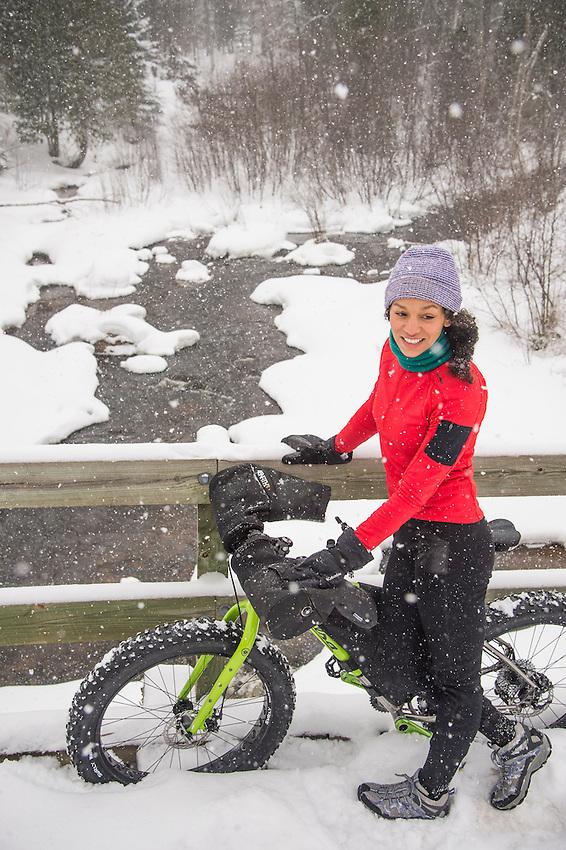 A winter cyclist on a fat bike rides trails along the Dead River in Marquette, Michigan.