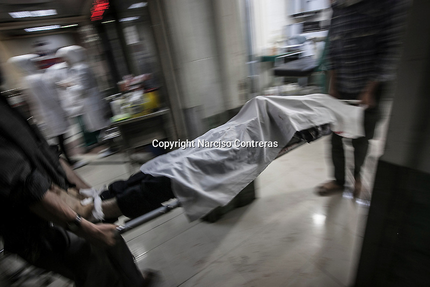 A dead body of Syrian civilian is carried out on a trolley as he arrives at the emergency ward of a hospital after has been killed by mortar shelling at the Arkub district in Aleppo City.