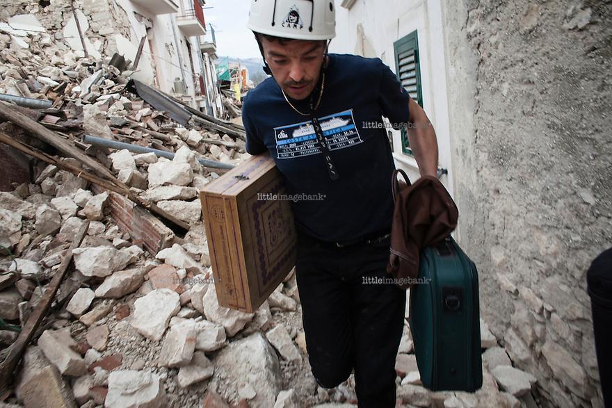 L'aquila, Abruzzo, Italia. 08.04.2009. Francesco Colaianni på vei ut av restene av sitt hjem i Onna med sine mest nødvendige eiendeler. Klokken 03:32 den 6 april 2009. Et jordskjelv som måler 6.3 ryster byen. 309 mennesker mister livet. Fem år senere sliter de som overlevde fortsatt med etterskjelvene, i form av en guffen cocktail av uærlige offentlige tjenestemenn, mafia og 494 millioner øremerkede euro på avveie. Fotografier til bruk i feature i DN lørdag 05.04.2014. Foto: Christopher Olssøn.
