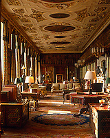 In the sumptuous library, the gilded stucco ceiling by Edward Goudge frames paintings by Antonio Verrio which date to the 17th century
