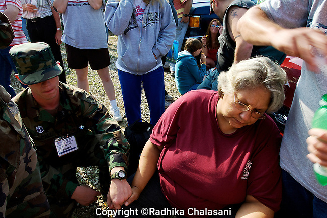 WISE, VIRGINIA-JULY 24: A member of the Virginia Defense Force holds the hand of a woman suffering from low blood sugar after waiting for hours to enter the Virginia-Kentucky Fairgrounds for free medical care provided by the Remote Area Medical (RAM) Expedition in the heart of the Appalachian mountains July 24,209. Many have slept overnight  in their cars, trucks, RVs or in tents waiting for a ticket number. The two and half-day event helped provide health care for 2,715 people, most of whom are uninsured or underinsured with unaffordable co-pays or high deductibles for their insurance policies. An army of seventeen hundred volunteers including individual doctors, nurses, members of the UVa medical and nursing schools, the Lions Club, and the Health Wagon helped organize the event and provide services. Organizers estimate that they provided over $1.6 million USD worth of care, spending approximately $250,000.
