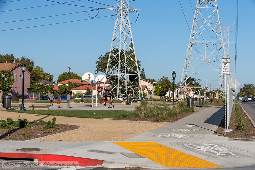 Many elements of State Street Park can be seen in this image: a wide paved path for pedestrians that's protected from the busy street, clearly marked bike paths, decomposed granite walking trails, lighting, and recreational areas (in this case: basketball courts with youths playing basketball).  Taken at the corner of Southern and Elizabeth.