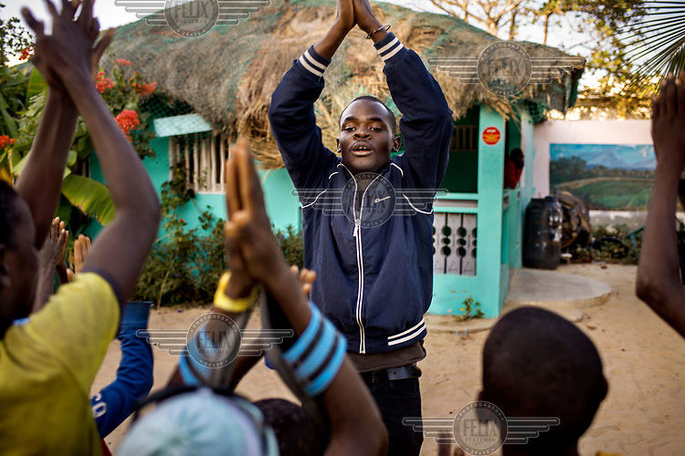 Abdourahmane Soumare, a teacher at the Maison de la Gare, leads a session of physical exercise with ex-Talibe. The Maison de la Gare is a charity that seeks to rehabilitate Talibe (children who live and study the Koran at a Daara, religious school). <br /> Talibe often have issues that stem from being separated from their parents at a young age and the abuse they endure at the Daaras where they are expected to beg to raise money for the Daara's marabout and to get food to fed themselves.