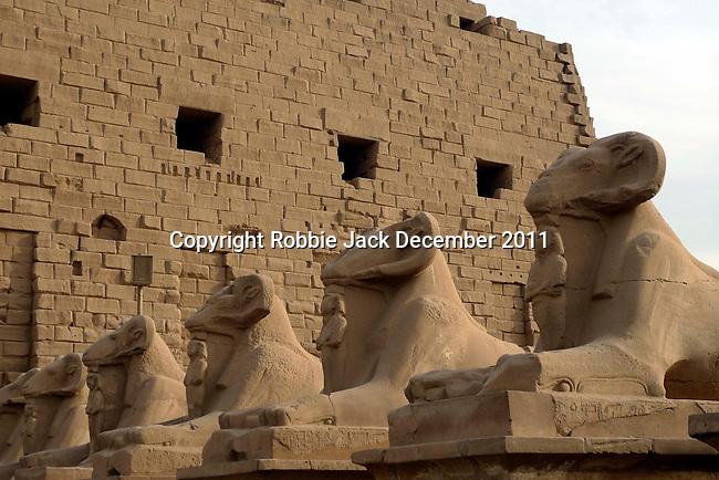 Avenue of ram-headed sphinxes (a symbol of the god Amun) with Ramses II leading to the first pylon at Karnak. Karnak is part of the ancient city of Thebes ( built in and around modern day Luxor).The building of the Temple complex at Karnak began in the reign of the Pharaoh Senusret I who ruled Egypt from 1971 -1926 BC. Approximately 30 Pharaohs contributed to the building of the complex and in so doing made it the largest ancient religious site in the world. The ancient name for Karnak is Ipet-isut (Most select of places).