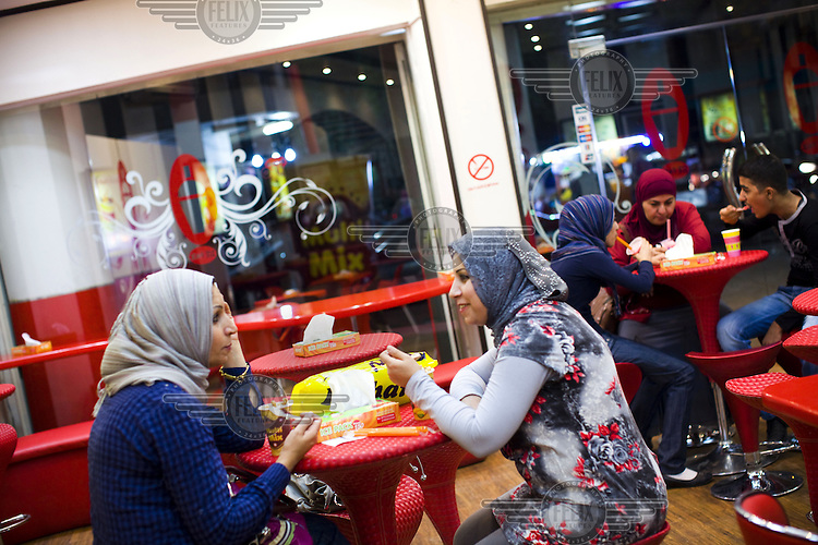 People enjoy a night out in the Karadah district of Baghdad. A recent attack in a church and bombings didn't stop many people going out in the evening.