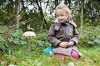 Young child observing a mushroom.