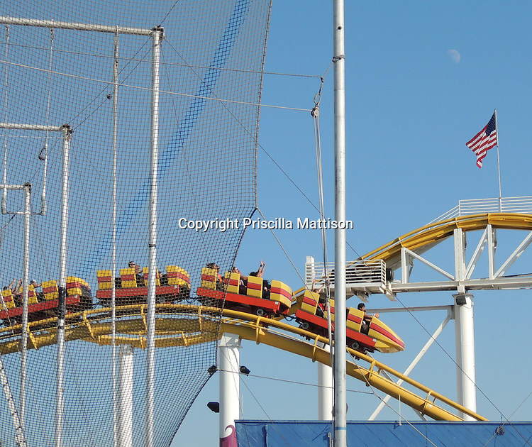 Santa Monica, California - September 23, 2012:  A roller coaster zooms by an American flag.