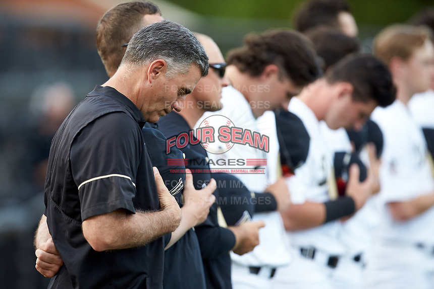 Wake Forest Demon Deacons head coach Tom Walter (16) bows his head during the National Anthem prior to the game against the North Carolina State Wolfpack at David F. Couch Ballpark on April 18, 2019 in  Winston-Salem, North Carolina. The Demon Deacons defeated the Wolfpack 7-3. (Brian Westerholt/Four Seam Images)