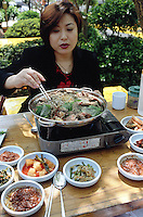 "Korea. South Korea. Incheon. 30 km from Seoul. A woman eats with her friends dog meat on a saturday lunch in a restaurant specialised with dog food.  ""Bosintang"" dish has dog meat cooked in a soup with various spices (ginseng, soya,..) and vegetables. On the side lies diferents plates with pickles, carots, cabbages,...  Dog meat is a delicatessen of korean traditionnal cooking.  © 2002 Didier Ruef"