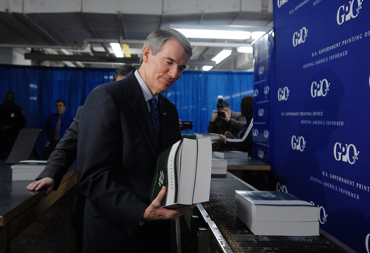 Office of Management and Budget (OMB) Director Rob Portman, inspects a copy of The Budget of the United States Government, Fiscal Year 2008, at the GPO while they roll of the presses.