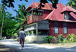 Man cycling past large old colonial corrugated iron home, La Digue island, Seychelles