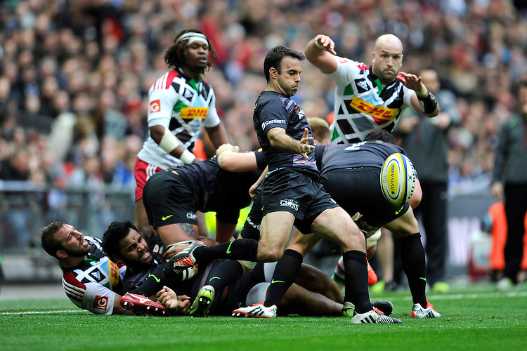 Neil de Kock of Saracens sends up a box kick as George Robson of Harlequins looks on