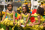Three young girls dance during the parade for the ZomerCarnaval (Summer Carnival) in Rotterdam, the Netherlands. The street parade is the colorful high point of the Rotterdam carnival. It is a tropical themed parade with over 2000 participants and travels 6km through the center of Rotterdam.