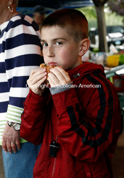 Woodbury, CT- 23 May 2014-052314CM05-  Caleb Roden, 9, enjoys a hamburger during the 2nd annual pig roast at Hollow Park in Woodbury on Friday.  The event was sponsored by The Resident State Troopers Office and Associates Substance Abuse Prevention (ASAP). The event was free to the community and featured food, music and games, including laser tag, video games and a rock climbing wall.  Resident State Trooper Sgt. Joe Roden said the event was held to bring the community together and interact with the police. The rain didn't deter the attendance with over 150 children and families coming together. Christopher Massa Republican-American
