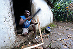 Abel Dupres chops firewood in the doorway of his home in Despagne, a rural village in southern Haiti where the Lutheran World Federation has been working with residents to improve their quality of life.