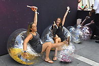 Guests at a Santa Margherita marketing event being photographed holding bottles of wine in bubble chairs for social media uploads.
