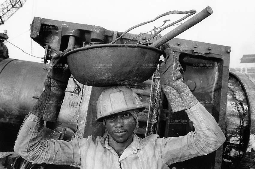 India. Province of Gujarat. Alang. A worker, a man with gloves and a helmet, carries on his head a metal bowl with various tools. Alang, located in the Gulf of Khambhat, is a ships breaking place. and is considered as the biggest scrapyard in the world. Ships recycling for its metals. Environmental issues. Hazardous waste. © 1992 Didier Ruef