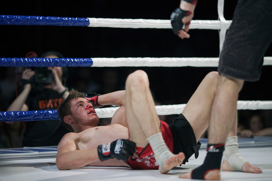 Moscow, Russia, 05/06/2010..A bloodied Marat Peksov lies on the canvas in a mix-fight bout during the new Fight Nights boxing tournament, featuring kick-boxing, boxing and mixed fighting.