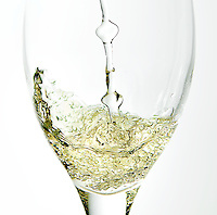 Action shot of white wine being poured into a glass.