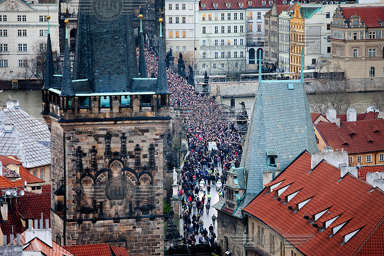 A large crowd, estimated at 10,000 strong, accompanies the funeral cortege of Vaclav Havel across the Charles Bridge towards Prague Castle.