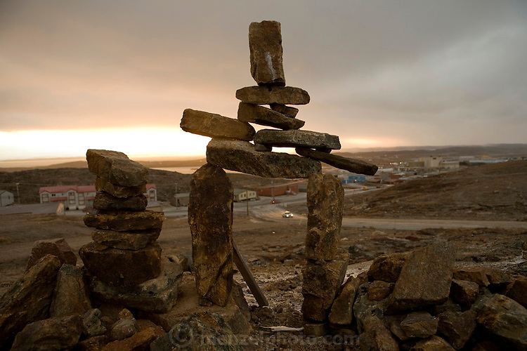 "Inukshuk (stone marker) above the town of Iqaluit, Nunavut, Canada. Iqaluit, with population of 6,000, is the largest community in Nunavut as well as the capital city. It is located in the southeast part of Baffin Island. Formerly known as Frobisher Bay, it is at the mouth of the bay of that name, overlooking Koojesse Inlet. ""Iqaluit"" means 'place of many fish'. The image is part of a collection of images and documentation for Hungry Planet 2, a continuation of work done after publication of the book project Hungry Planet: What the World Eats, by Peter Menzel & Faith D'Aluisio.."