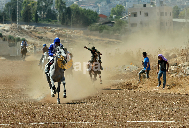 Palestinian jockeys ride their horses during a race in the West Bank city of Nablus on Aug  21, 2012. Hundreds of Palestinians from all over the West Bank gathered to follow the horse race on Tuesday in the northern West Bank city. Photo by Nedal Eshtayah