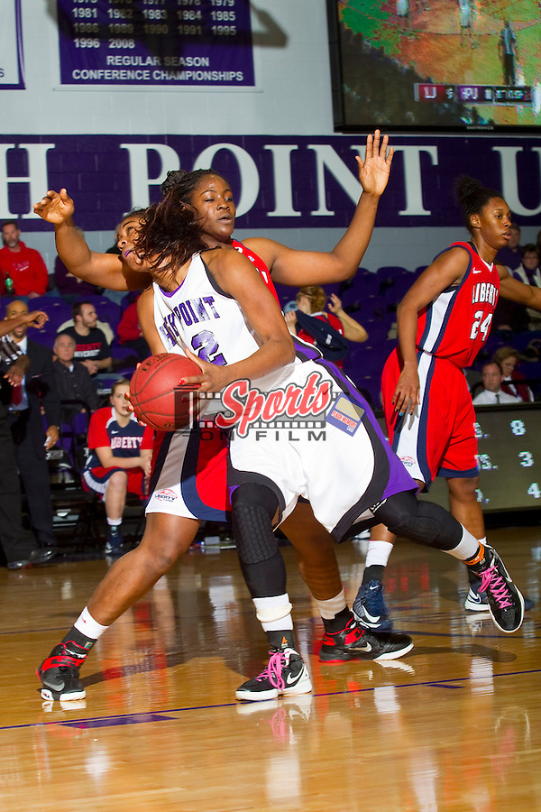 Cheyenne Parker (42) of the High Point Panthers attempts to drive to the basket past Tolu Omotola (22) of the Liberty Flames at Millis Athletic Center on February 2, 2013 in High Point, North Carolina.  The Flames defeated the Panthers 67-59.   (Brian Westerholt/Sports On Film)
