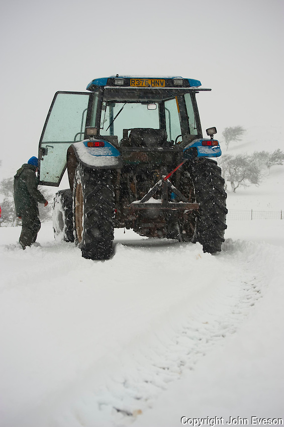 Man getting into a New Holland tractor during a snow storm, Whitewell, Lancashire.