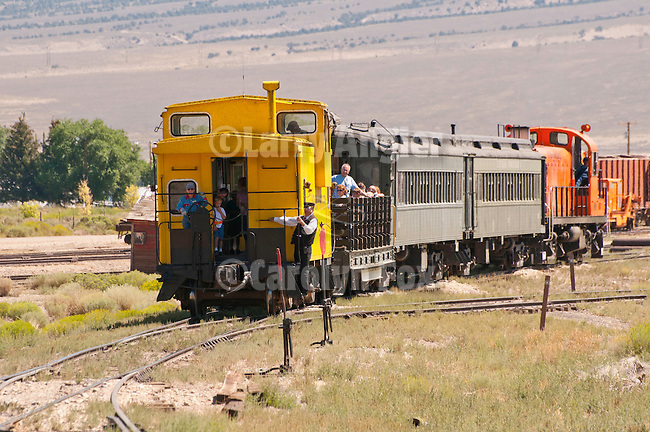 1950s, former Kennecot Nevada RS-2 locomotive pulls passenger cars and yellow caboose with passengers to the depot in Ely, Nev.