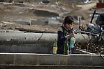 March 29, 2011, Minamisanriku, Miyagi, Japan - More than two weeks after the tsunami the rural area between Kesennuma and Minamisanriku lies in ruin. Koyo Okoshi (9) helps locate bottles of sake from her father's business. (Photo by Wesley Cheek/AFLO) [3682].