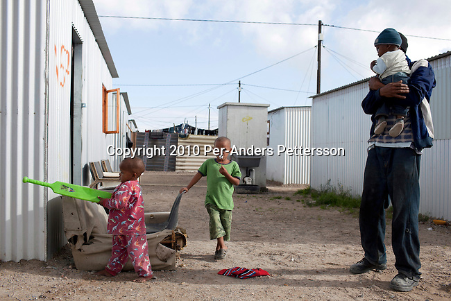 """CAPE TOWN, SOUTH AFRICA - MAY 3: Children play among tin houses on May 3, 2010, in Blikkiesdorp about 40 kilometers south of Cape Town, South Africa. Blikkiesdorp, which is Afrikaans for """"Tin Can Town"""", was given its name by its residents because of the row-upon-row of tin-like shacks made of corrugated iron. It was built by the City of Cape Town in 1997 and about 1600 one-roomed shacks were built. It has been known for its bad conditions and a dumping ground for shack dwellers from other areas around Cape Town. Recently many street people in Cape Town has been forcefully removed and relocated to this place. The ones that have refused has been put in holdings cells or prisons such as Pollsmoor Prison. This campaign has identified in the preparation for the soccer World Cup, who starts on June 11, 2010 and goes on for a month. The City of Cape Town doesn't want international visitors to be hassled by street people. (Photo by Per-Anders Pettersson)"""