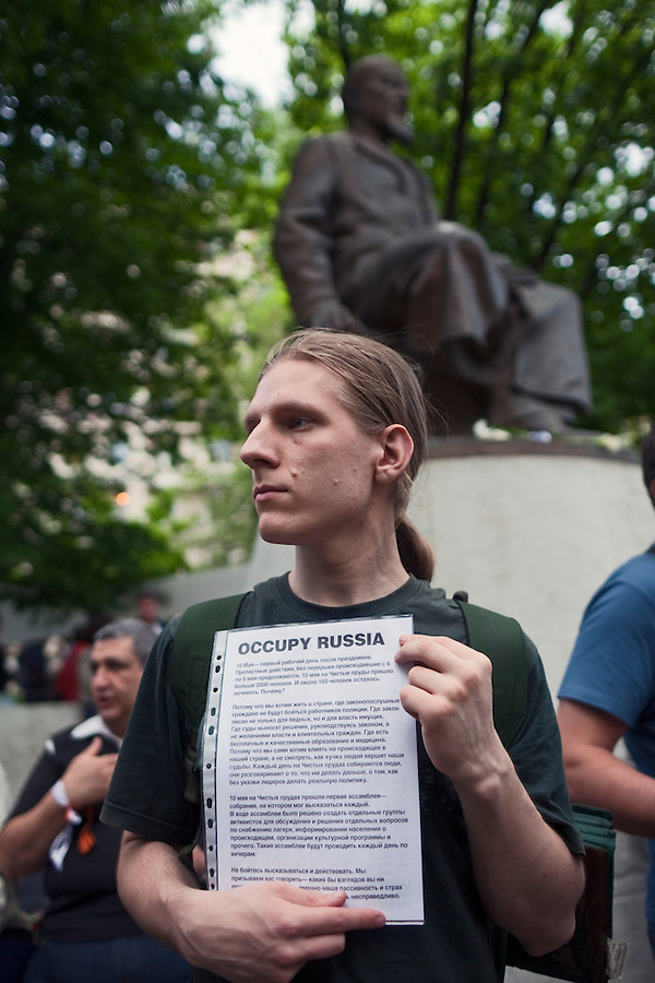"Moscow, Russia, 12/05/2012..A protester under  the statue of Kazakh poet Abai Kunanbaev hold a sign ""Occupy Russia"" in Chistiye Prudy, or Clean Ponds, a park in central Moscow were some 200 opposition activists have set up camp."