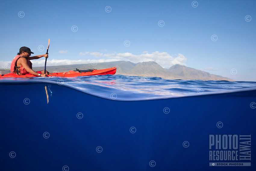 A young man paddling a kayak off the coast of Maui, with Olowalu Pass in the background.