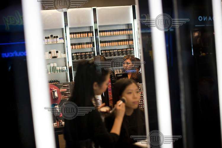 Women have make-up applied in a shop in a commercial area of central Hong Kong.