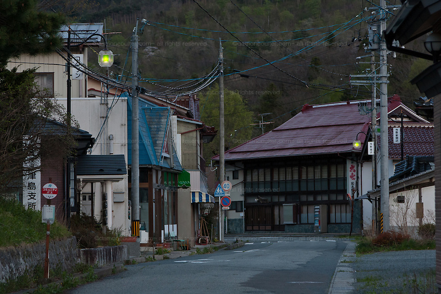 Street lights come on as evening arrives in the abandoned village of Tsushima in Fukushima, Japan. Friday May 4th 2012. After the explosions at the Daichi nuclear plant caused by the March 11th 2011 earthquake and tsunami, High levels of radioactive contamination in this village has made it uninhabitable.