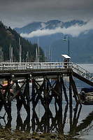 jetty at Deep Cove Bay with clouds above the mountains over Mount Seymour provincial park. Deep Cove, Burrard Inlet, Vancouver, British Columbia, Canada.