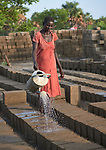 A woman waters newly formed concrete blocks to keep them from drying too quickly at the Loreto School in Rumbek, South Sudan. The school is run by the Institute for the Blessed Virgin Mary--the Loreto Sisters--of Ireland. The blocks are being used to construct new classrooms.