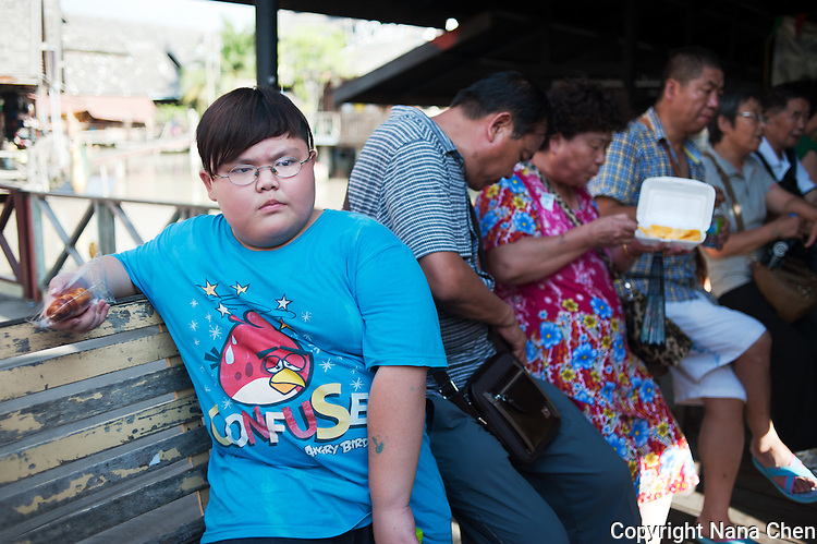 A row of Chinese tourists break from the heat at the Pattaya Floating Market, one of the most frequented attractions in the city. A boy looks onto a crowd of Chinese tourists as his father takes photos of him.
