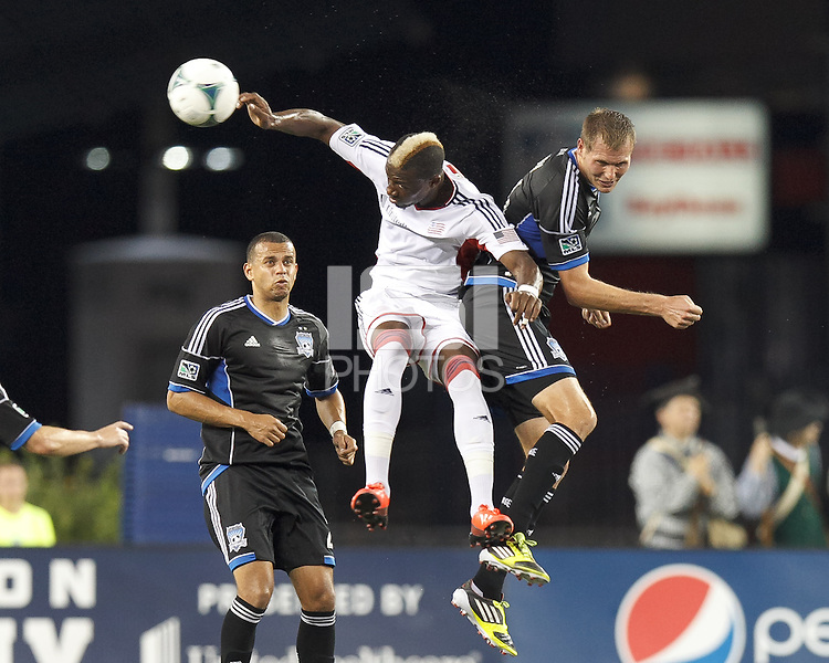 New England Revolution substitute forward Dimitry Imbongo (92) and San Jose Earthquakes forward Adam Jahn (14) battle for head ball.  In a Major League Soccer (MLS) match, the New England Revolution (white) defeated San Jose Earthquakes (black), 2-0, at Gillette Stadium on July 6, 2013.