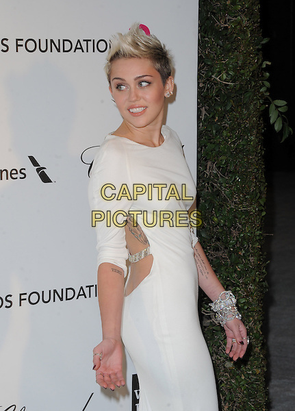 Miley Cyrus (wearing Azzaro).The 21st Annual Elton John AIDS Foundation Academy Awards Viewing Party held at The City of West Hollywood Park in West Hollywood, California, USA..February 24th, 2013.oscars half length dress white long sleeves diamond bracelets chains straps backless back behind rear looking over shoulder side tattoos.CAP/DVS.©DVS/Capital Pictures.
