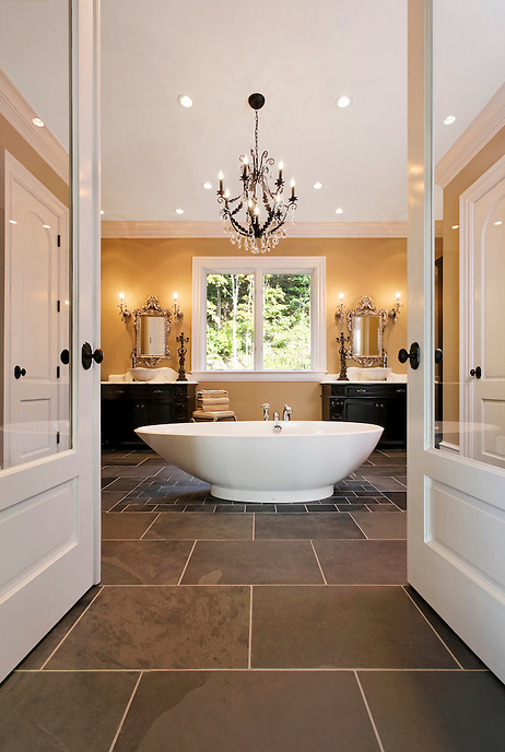 Traditional master bath with contemporary pedestal tub, wrought iron crystal chandelier, dual sinks, framed by glass french doors