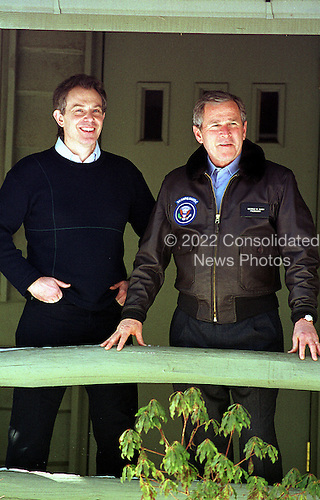 """Thurmont, MD - February 23, 2001 -- United States President George W. Bush and Prime Minister Tony Blair of Great Britain enjoy the view from the porch of the """"Holly"""" cabin at Camp David, near Thurmont, Maryland on February 23, 2001..Credit: Martin H. Simon - Pool / CNP"""