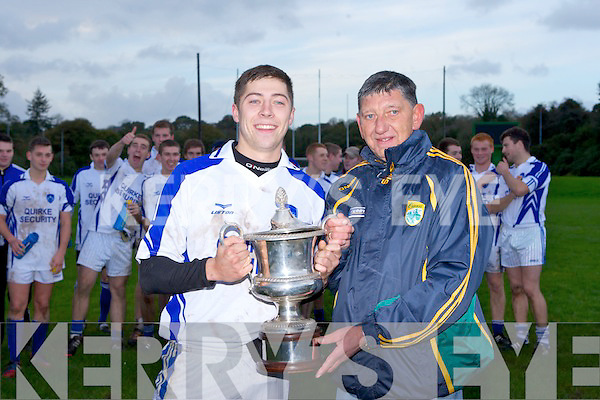 Kerins O'Rahillys captain Kieran O'Mahony is presented the cup by Ger Galvin after they defeated Templenoe in the U21 club Championship final in Killarney on Saturday