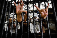 "Members of the Mara Salvatrucha gang (MS-13) show hand signs, representing their gang, in a cell at the detention center in San Salvador, El Salvador, 20 February 2014. Although the country's two major gangs reached a truce in 2012, the police holding cells currently house more than 3000 inmates, five times more than the official built capacity. Partly because the ordinary Mara gang members did not break with their criminal activities (extortion, street-level distribution of drugs, etc.), partly because Salvadorean police still applies controversial anti-gang law which allows to detain almost anyone for ""suspicion of gang membership"". Accused young men are held in police detention centers where up to 25 inmates may share a cell of five-by-five metres. Here, in the dark overcrowded cages, under harsh and life-threatening conditions, suspected gang members wait long months, sometimes years, for trial or for to be transported to a regular prison."