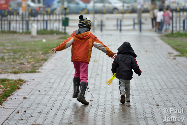 Two refugee children walk in a city park in Belgrade, Serbia. The park has filled with refugees from several countries stopping over on their way to Germany, Sweden, Holland, and elsewhere.