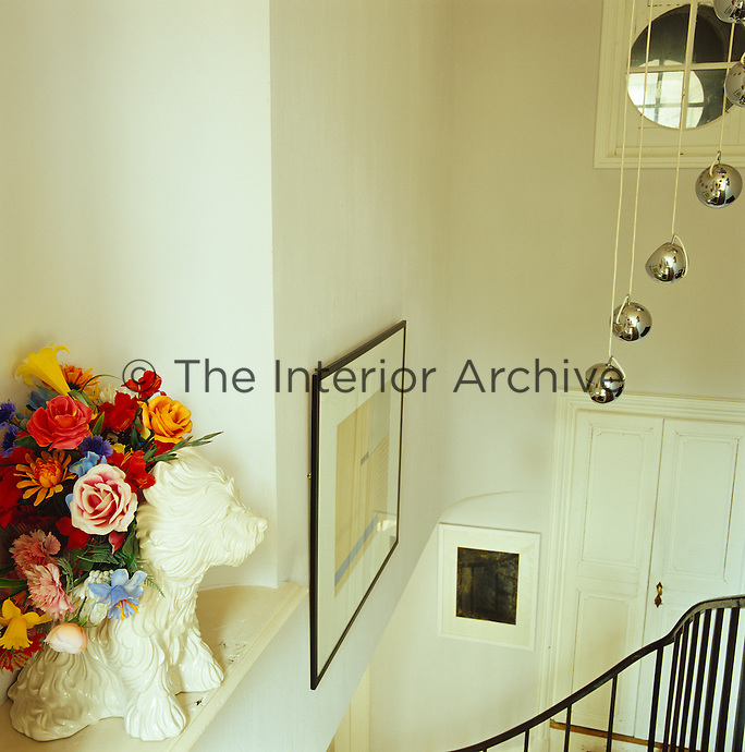 A Jeff Koons white terrier puppy vase full of plastic flowers sits on a niche in the stairwell