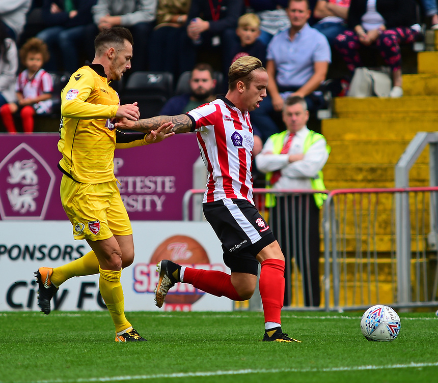 Lincoln City's Jordan Maguire-Drew holds off the challenge from Morecambe's Michael Rose<br /> <br /> Photographer Andrew Vaughan/CameraSport<br /> <br /> The EFL Sky Bet League Two - Lincoln City v Morecambe - Saturday August 12th 2017 - Sincil Bank - Lincoln<br /> <br /> World Copyright &copy; 2017 CameraSport. All rights reserved. 43 Linden Ave. Countesthorpe. Leicester. England. LE8 5PG - Tel: +44 (0) 116 277 4147 - admin@camerasport.com - www.camerasport.com