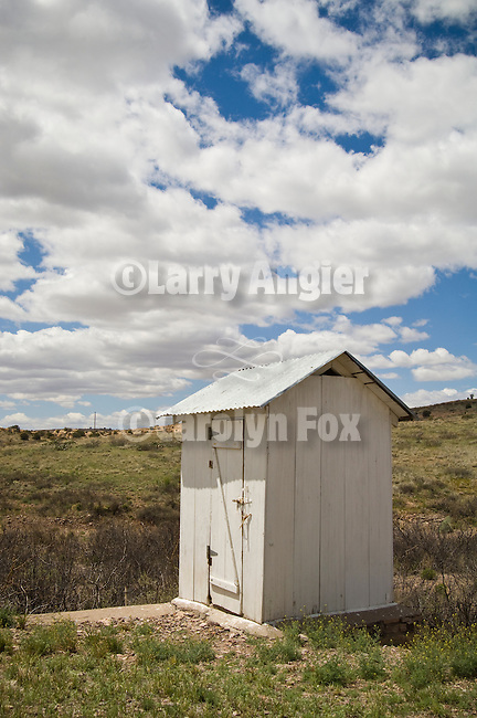 White-washed outhouse, clouds, rural New Mexico