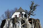 """Foto: VidiPhoto<br /> <br /> LENT – Na drie flinke stormen is er maandag van het bekende kunstwerk """"Altijd Lente"""" bij het dorp Lent weinig meer over. Het aluminiumfolie om de houten constructie van de 'terp' is vrijwel volledig weggeblazen. Het kunstwerk van Leonard van Munster, een boerderij met een boom vol bloesem, is volgens de maker een vorm van verzet tegen de landhonger van Nijmegen, aan de overzijde van de Waal. """"Altijd Lente"""" is tevens een eerbetoon aan de inwoners van het dorp die vanwege de nieuwbouw van de stad (Waalsprong) en de aanleg van de nevengeul moesten verhuizen. Het is een exacte kopie in miniatuur van een boerderij die ooit in Lent stond. Het kunstwerk staat tijdelijk op deze plek. Naar een definitieve locatie wordt nog gezocht, waarbij de terp ook weerbestendiger wordt gemaakt."""